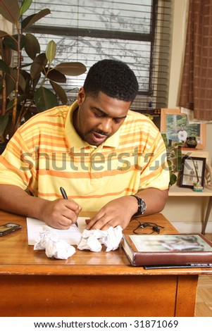 Man sitting at desk, trying to write - stock photo