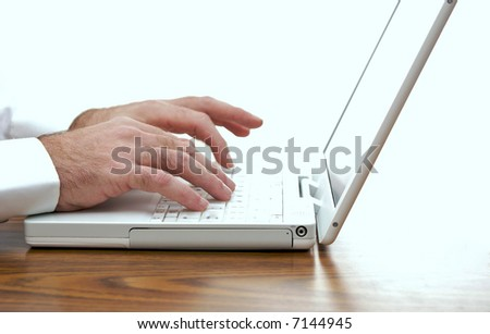 man sitting at desk typing on the keyboard of a white laptop - stock photo