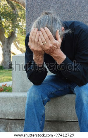 Man sitting at gravesite with his head in his hands - stock photo