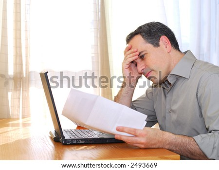Man sitting at his desk with a laptop and bills  looking concerned - stock photo