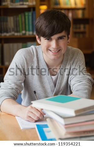 Man sitting at library desk at the college library smiling