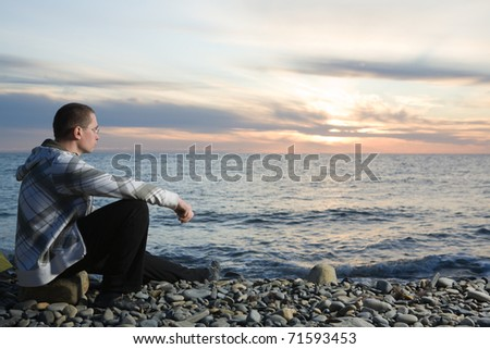 Man sitting at pebbly beach at sunset