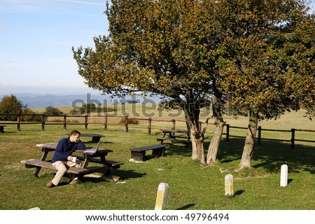 Man sitting at picnic table using laptop - stock photo