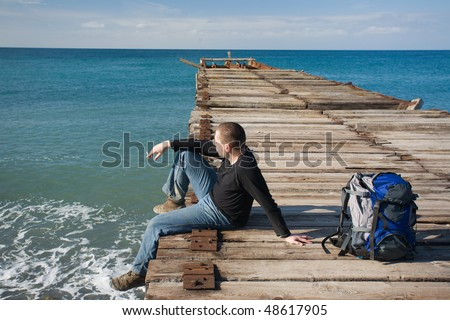 Man sitting at pier and looking at the sea