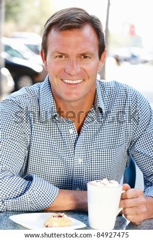 Man sitting at sidewalk cafe - stock photo