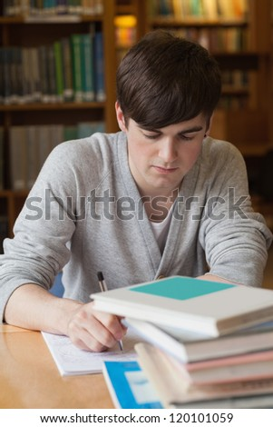 Man sitting at table at the library writing