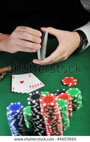 man  sitting at the gambling table and  playing cards