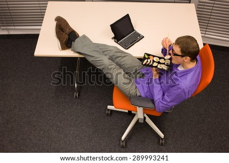 man sitting at with legs on the desk, heaving break in work eating sushi with chopsticks in office - stock photo