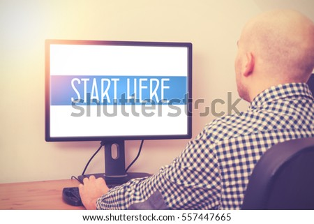 man sitting behind a computer searching things about Start Here - startup concept