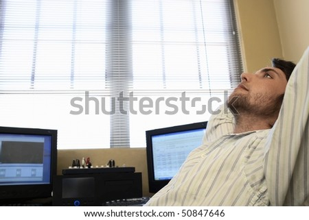 Man sitting by computers, relaxing, side view. - stock photo