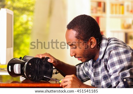 Man sitting by desk repairing small coffee maker using screwdiver, smiling happily while working
