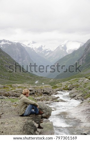 Man sitting by stream and mountains