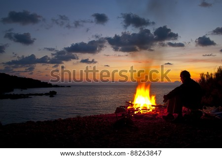 man sitting by the fire and looking to somewhere - stock photo