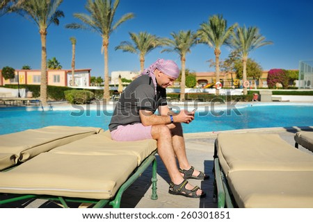 man sitting by the pool and looking at the smartphone. - stock photo