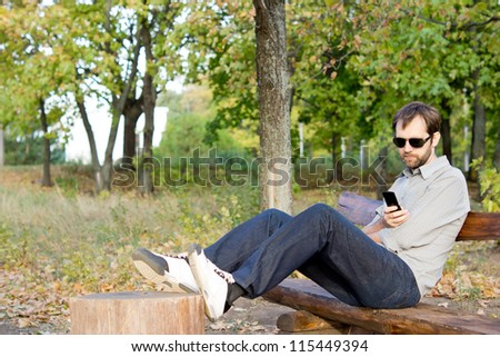 Man sitting comfortably on a wooden park bench with his feet up reading a message on his mobile phone with copyspace