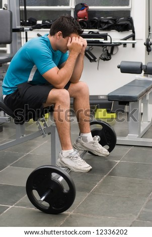 Man sitting down on a weight bench at the gym with his head in his hands and a barbell on the floor in front of him - stock photo
