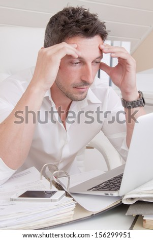 Man sitting frustrated at office looking at his liabilities. - stock photo