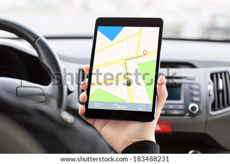 man sitting in a car, holding a touch tablet with a GPS  navigator on the screen. - stock photo