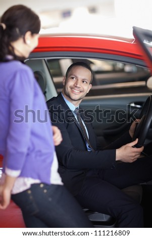 Man sitting in a car while talking to a woman in a car shop - stock photo