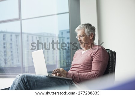 Man sitting in a leather chair using laptop