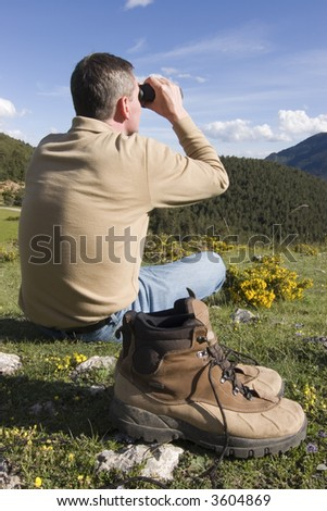 Man sitting in a meadow in the mountains looking through binoculars - stock photo