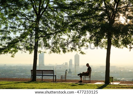 Man sitting in a park on a sunny morning in Lyon, looking at his phone.