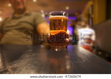 Man sitting in a pub or bar with a glass of beer - stock photo