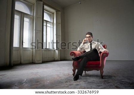 Man sitting in a red armchair - stock photo