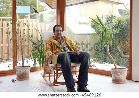 man sitting in a rocking chair inside conservatory and having a cup of coffee - stock photo