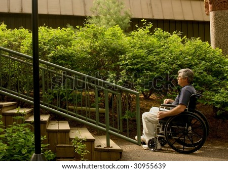 man sitting in a wheelchair contemplating a set of stairs - stock photo