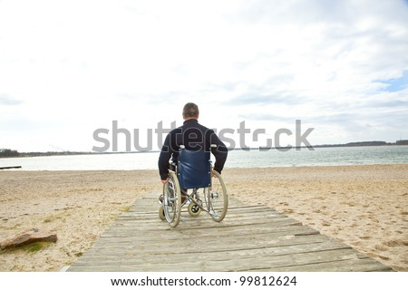 Man sitting in a wheelchair on the beach