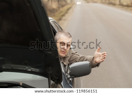 Man sitting in broken car  on the road - stock photo