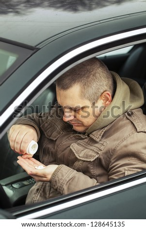 Man sitting in car with drugs in the hands - stock photo