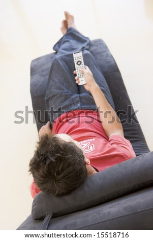 Man sitting in chair using remote control - stock photo