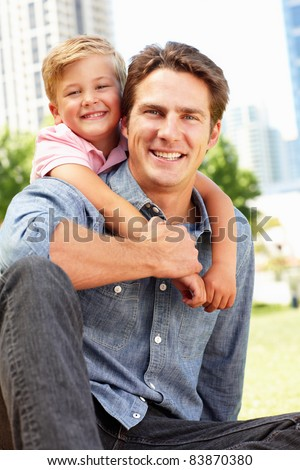 Man sitting in city park with young son - stock photo