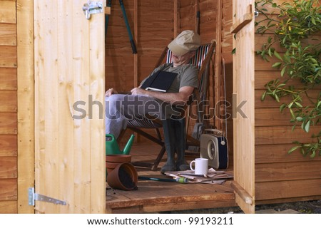 Man sitting in deckchair falling asleep in the shed while reading book - stock photo