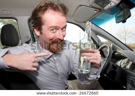 Man sitting in drivers with a bottle alcohol - stock photo