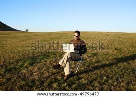 Man sitting in field with laptop - stock photo