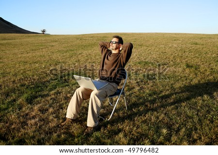 Man sitting in field with laptop and relaxing - stock photo