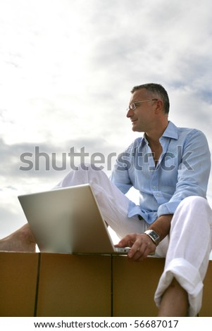 Man sitting in front of a laptop computer on a terrace - stock photo