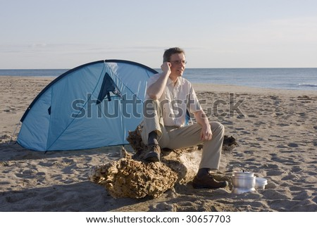Man sitting in front of his tent on a beach while making a phone call - stock photo