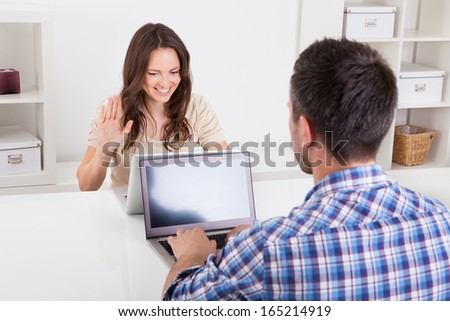 Man Sitting In Front Of Woman Looking At Laptop