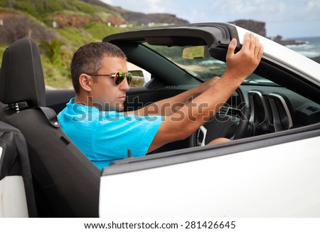 Man sitting in his white luxury sports car, enjoying freedom feeling happy on the Hawaiian beach, Oahu, Hawaii, USA.