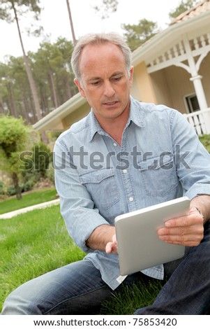 Man sitting in home garden with touchpad - stock photo