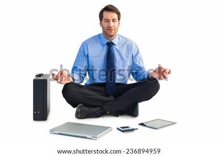 Man sitting in lotus pose with laptop, tablet and suitcase on white background