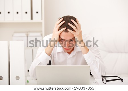 man sitting in office resting his forehead in hands - stock photo