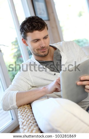 Man sitting in sofa with electronic tablet - stock photo