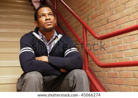 Man sitting in Stairwell - stock photo