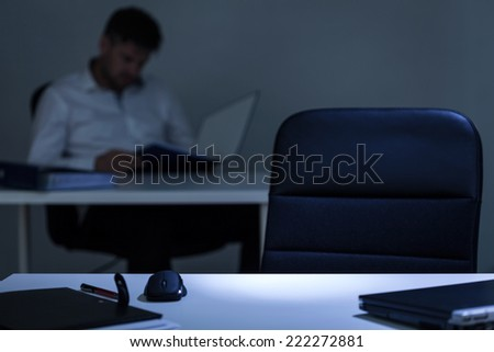 Man sitting in the background of empty office desk - stock photo