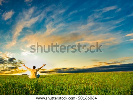 man sitting in the field under sunset